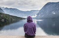 Sporty woman watching tranquil overcast morning scene at lake Bohinj, Alps mountains, Slovenia.
