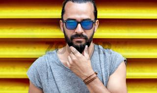 close up of man in sunglasses touching beard