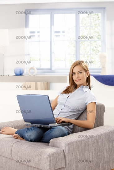 Attractive woman browsing internet at home