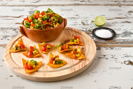 Nachos chips and vegetables in an earthenware bowl and tequila