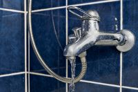 Chromium-plate tap angle view with water flow out frozen in air front view on blue color tiled wall