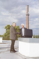 Senior businessmen handshaking while making a business deal on the roof of a building