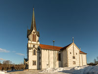 Bamble Church, large wooden church buildt in 1845. Winter, snow, sunshine and blue sky. Side view. Horizontal image.