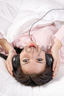 teenage girl listening to the music on the bed