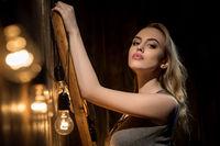 Blonde with long locks portrait near wooden wall