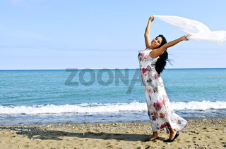 Beautiful young woman at beach with white scarf