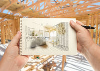Hands Holding Pen and Pad of Paper with Bathroom Design Inside House Construction Framing.