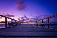 Wooden pier on the sea beach at sunset
