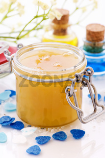 Honey in a preserving jar with two flasks with massage oil in background