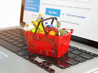 Shopping basket with variety of grocery products ion laptop keyboard. E-commerce concept