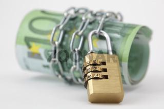 Geldscheinrolle mit Kette und Schloss