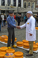 Farmer and cheese merchant bargain over the price of Gouda cheese, Gouda, Netherlands
