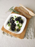 Marinated mozzarella with black olives, olive oil and mustard leaves