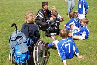 Junge im Rollstuhl schaut seinen Spielkameraden zu
