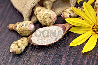 Flour of Jerusalem artichoke in spoon with vegetable on board