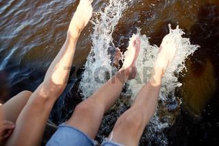 legs of couple splashing water in river