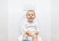 Adorable young child sitting and learning how to use the toilet