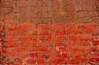 Old brick wall half painted in deep red, half in brown. Abstract background old red-brown brick wall