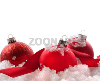 Red christmas balls and ribbon in snow on white