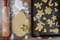 Top view of a baking sheet with a holiday shaped sugar cookies, with raw dough and rolling pin on th