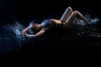 Sexy girl lying in water in the dark