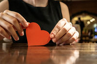 Female hands holding red paper heart and copyspace