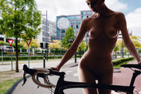 Naked woman with bicycle on a empty road