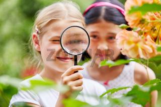 Mädchen betrachten Blumen durch  Lupe