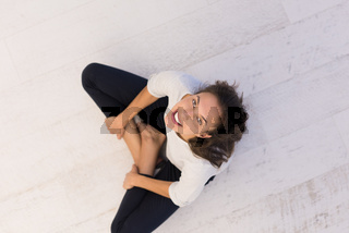 top view of young woman sitting on the floor