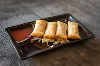 Fried spring rolls on black iron plate