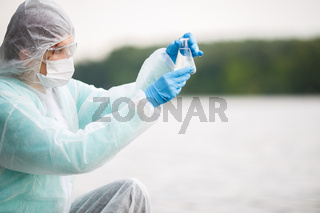 Chemist looks at water flask