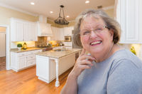 Happy Senior Woman In Custom Kitchen Interior
