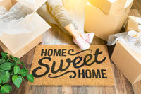 Woman Wearing Sweats Relaxing Near Home Sweet Home Welcome Mat, Moving Boxes and Plant.