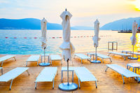 Beach with deckchairs and umbrellas at sundown
