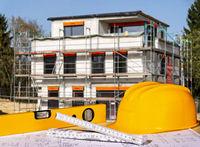 Construction site with helmet, spirit level, folding rule and blueprints