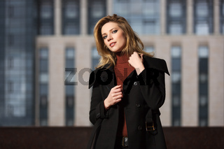 Fashion blond woman in black coat walking on the city street
