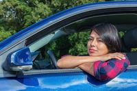 Colombian woman  enjoying the sun behind car wheel