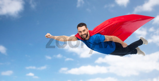 happy man in red superhero cape flying over sky