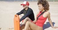 Smiling lifeguards sitting on beach