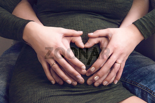 Heart shaped hands over a belly of pregnancy