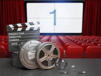 Cinema, movie or home video concept background. Film reels and clapper board in the theater movie cinema screen with empty seats.