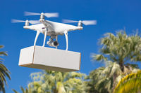 Unmanned Aircraft System (UAV) Quadcopter Drone Carrying Blank Package Over Tropical Terrain.