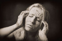 woman covered in dry cracked clay mask holding her head