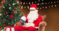 santa claus with tablet pc and christmas tree