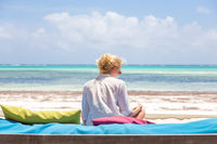 Relaxed woman in luxury lounger, arms rised, enjoying summer vacations on beautiful beach.