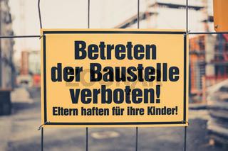 Yellow sign in german: Betreten der Baustelle verboten! Eltern haften für ihre Kinder! translation: entering the building site prohibited. Parents are responsible for their children