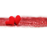 Red textile hearts on glitters
