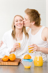Breakfast kissing couple enjoy orange juice