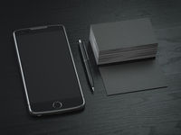 Mockup of black blank business cards,  black mobile phone and pen on  the black wooden desk background.