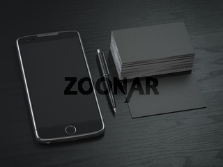Mockup of black blank business cards,  black mobile phone and pen on  the black wooden desk background.